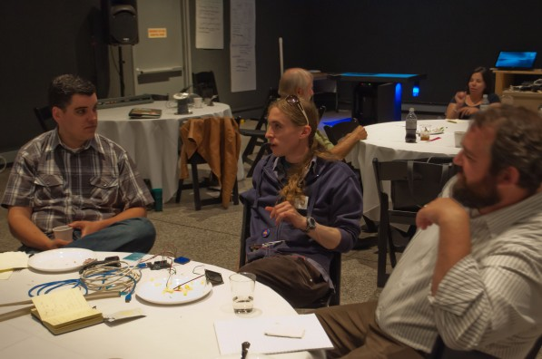 Photo of CMME workshop participants sitting at a table, talking to each other